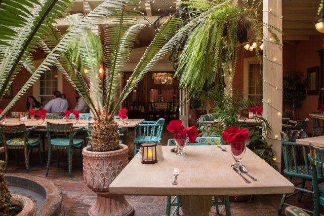 Restaurant setting with red table cloths and palms
