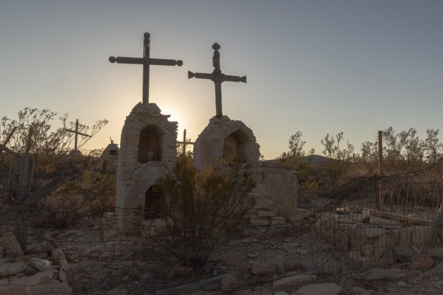 Two memorials with crosses at sunset