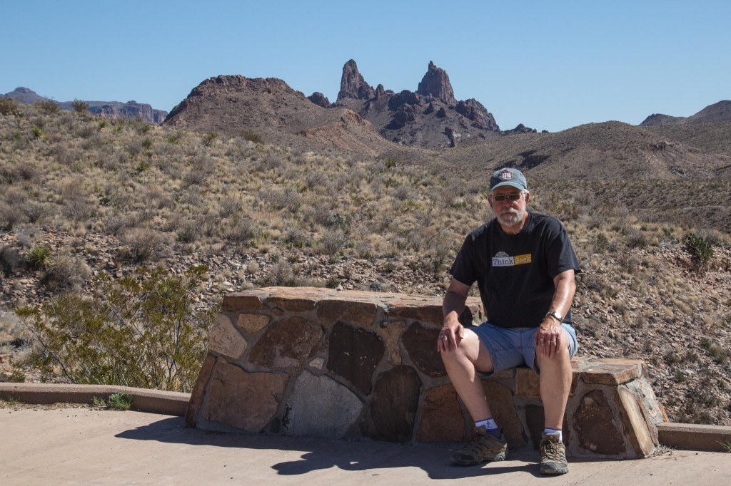 Man sitting on bench and Mule Ears Peaks