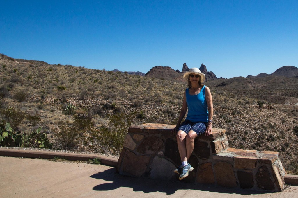 Woman sitting on bench and Mule Ears Peaks
