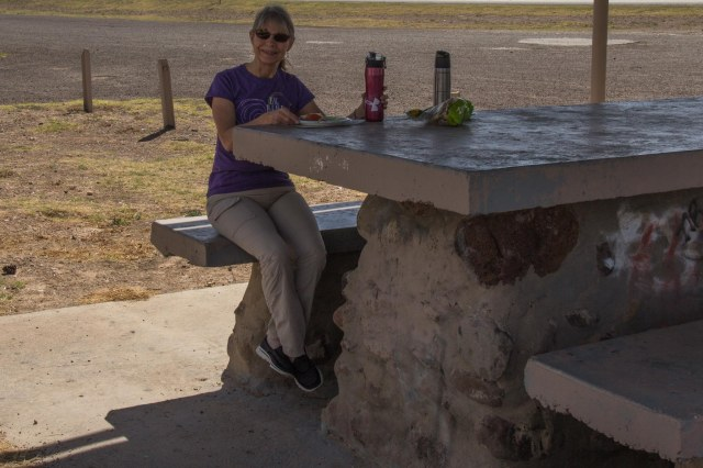 Woman sitting at oversized picnic table