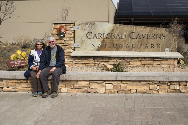 Two people sitting near Carlsbad Caverns National Park sign