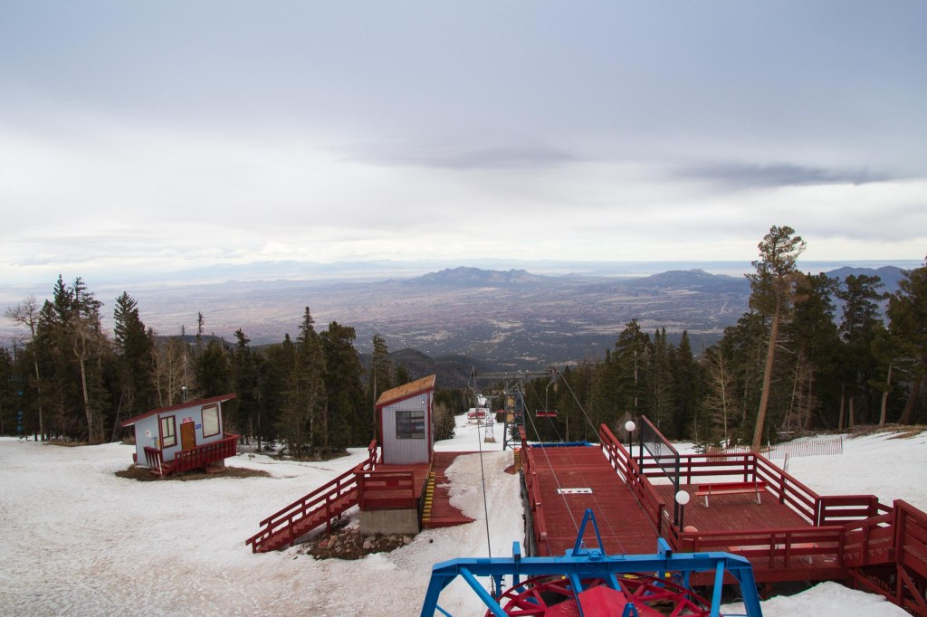 Red ski lift with valley below and cloudy skies