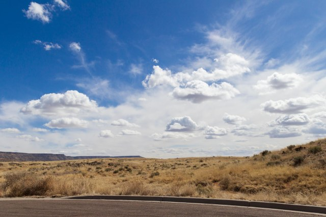 Blue skies with puffy white clouds and desert foreground