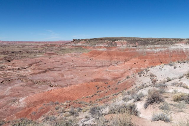 Green plateau with pink and red cliffs under blue sky