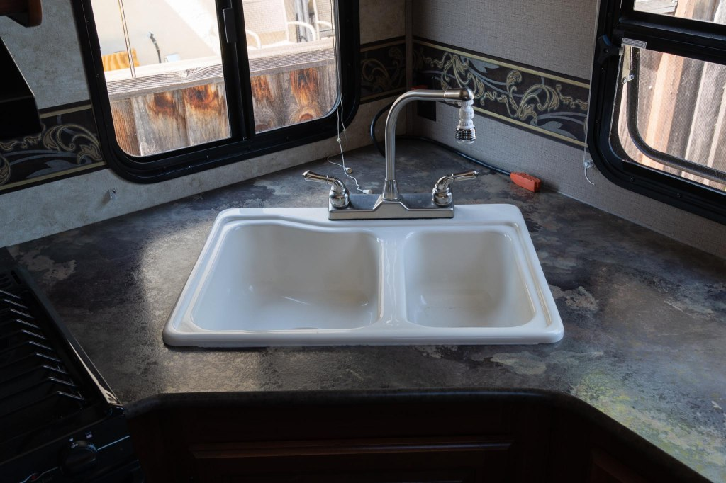 White double sink and faucet on RV kitchen counter