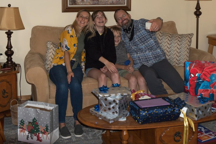 Man, woman, teen girl, and young boy on a couch with presents in foreground