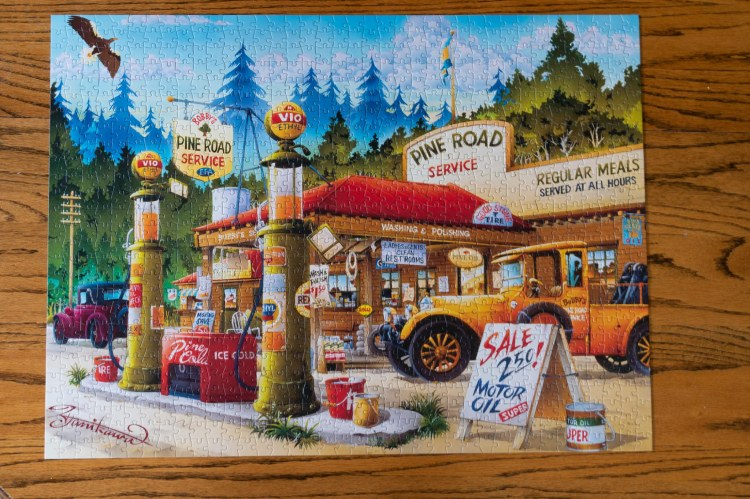 Puzzle of old time gas station, old time cars, and trees in the background, cloudy skies, and eagle flying
