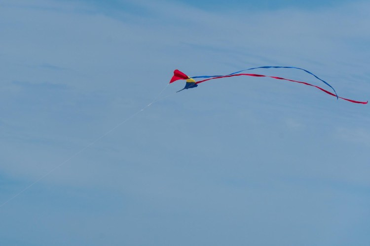 Red, yellow, and blue kite with red and blue streamers against the sky