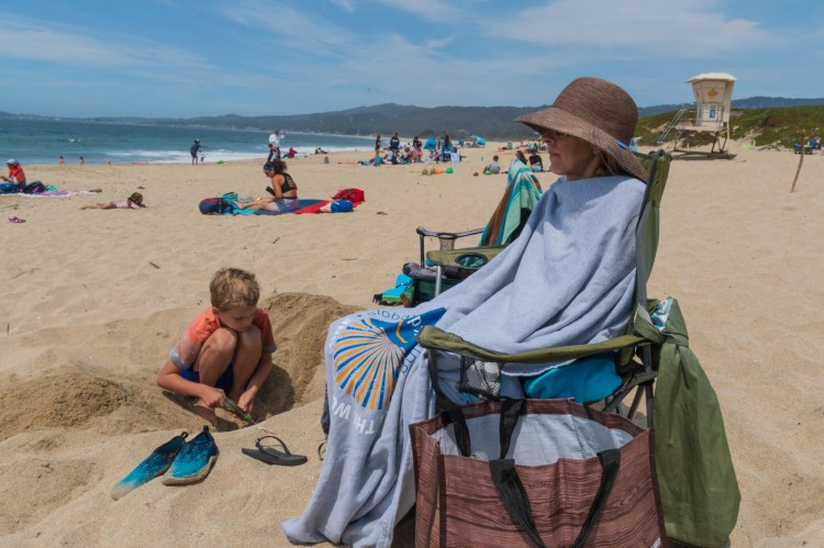 Boy digging in sand on beach and woman wrapped in towel sitting in a chair