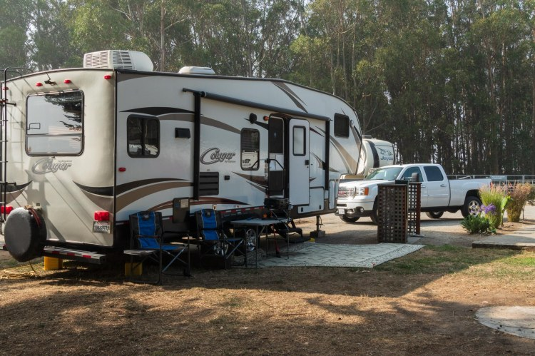 Fifth wheel trailer and white pickup campsite