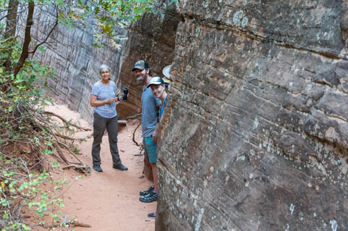 Three people standing next to rock cliff