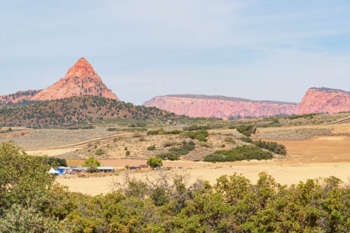 Pointy peak and mesas with shrubs and yellowed grass in foreground