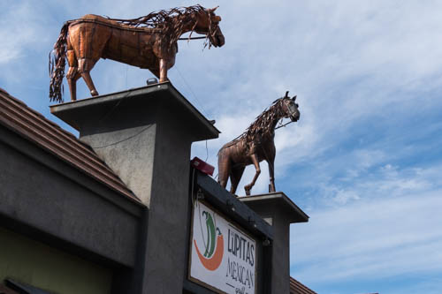Two horse sculptures atop a sign