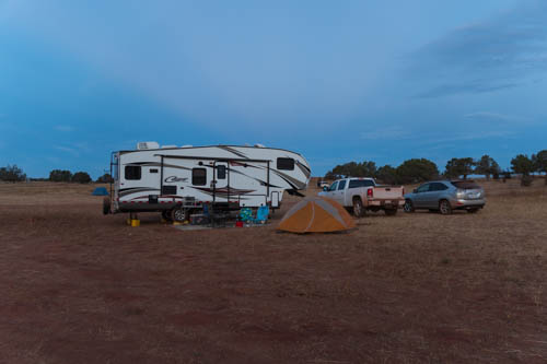 Fifth wheel trailer, white pickup, gray Lexus, and yellow tent