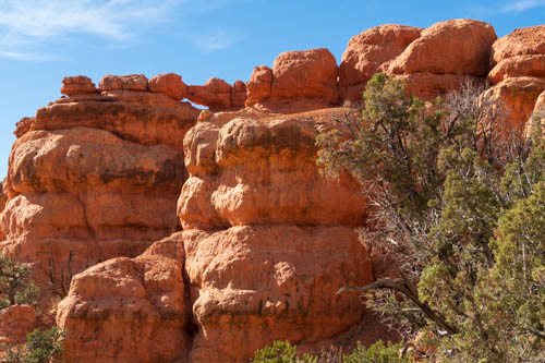 Red rock formations, arch, and blue sky
