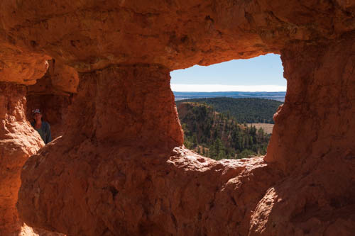 Landscape view through arch in rock formation, a person hidden in the shadows
