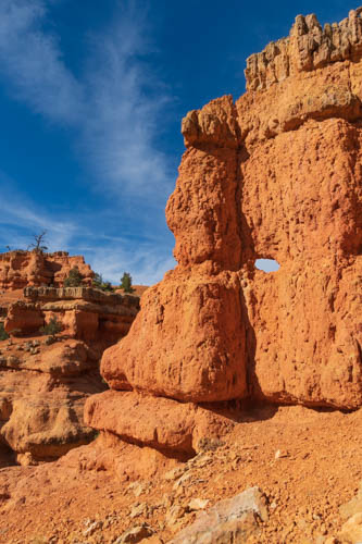 Red rock formations, hole in the rock, blue skies, wispy clouds