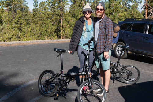 Man and woman posing with foldable bicycles