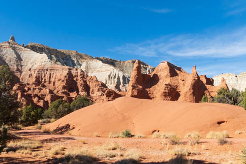 Red rock formations against back drop of tan and white formations.