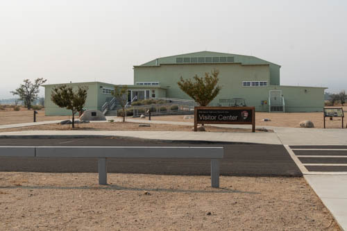 Desert landscape with large green building and signs