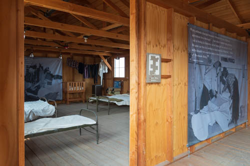 Inside wood barracks with cots, bedding, hanging clothes and information signs.