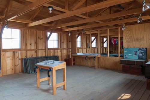 Inside wood framed barracks showing information signs