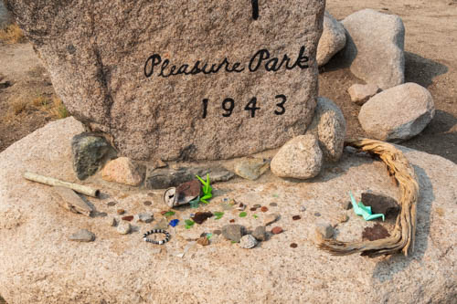 Coins, bracelets, origami and other trinkets at foot of Pleasure Park 1943 sign