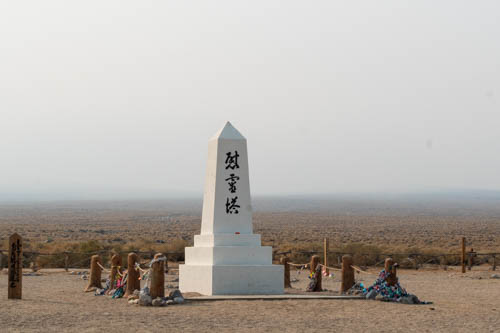 White obelisk with black Japanese characters, Soul Consoling Tour, smoky skies