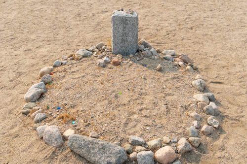 Round gravesite outlined with rocks in the sand and headstone