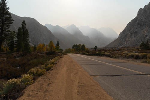 Road leading to mountain peaks shrouded in smoke