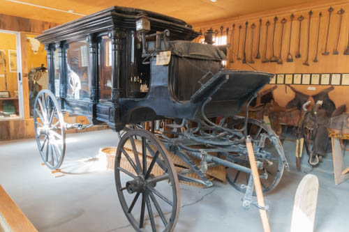 Black horse-drawn hearse inside building with western memorabilia