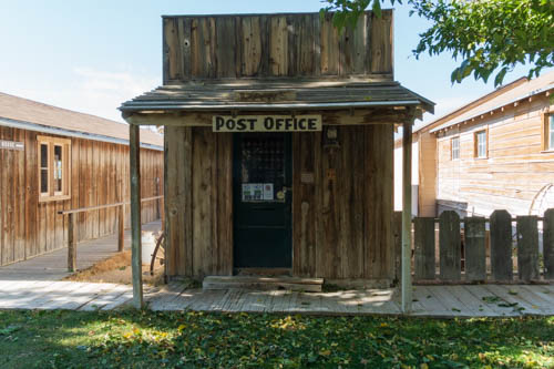 Small weathered wood building with Post Office sign