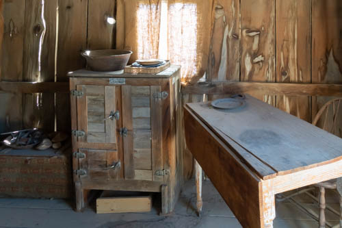 Table and icebox inside a miner's shack