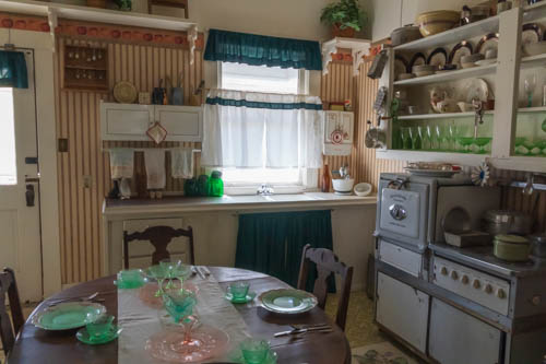 Early 1900s kitchen with stove, table, and dishware