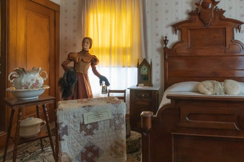 Inside early 1900s home showing a mannequin in period costume, wood carved bed, quilt, water pitcher, and bowl
