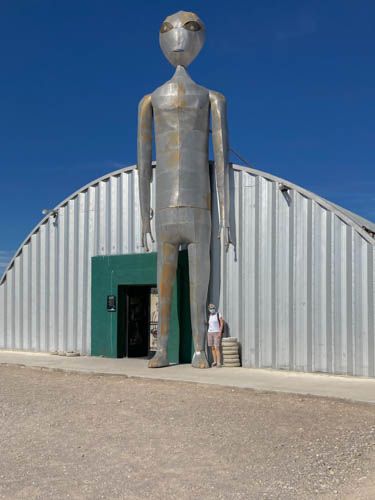 Aluminum space alien statue in front of a Quonset hut with woman standing up to its knee