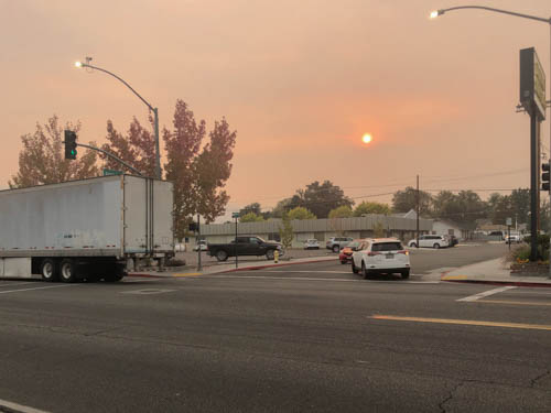 Street corner, semi trailer, cars, and setting sun obliterated by smoke in the air