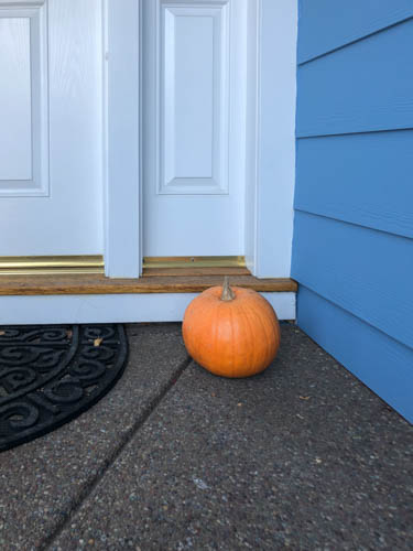 Pumpkin on doorstep of blue house with white trim