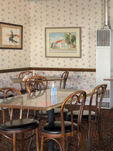 Wallpapered dining room with cane seats and rectangle tables
