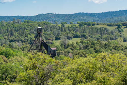 Headframe mining equipment towering over green leafed trees