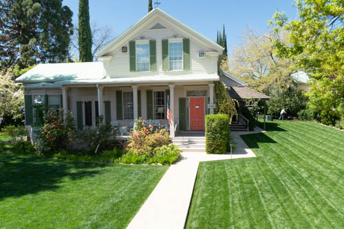 1800s style home with manicured green grass