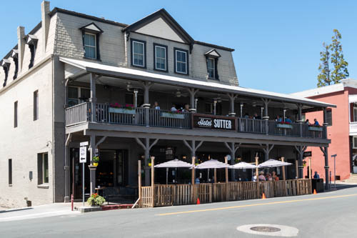 Beige 1800s style three story building used as Hotel Sutter with street dining under umbrellas